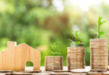 Opłata adiacencka to opłata od wzrostu wartości nieruchomości. Dlatego warto wiedzieć, kiedy należy ją uiścić. Na zdjeciu drewniany domek - figurka oraz monety ułożone w stosy.